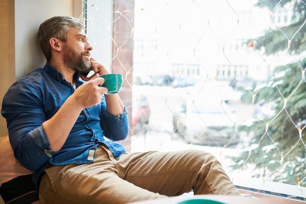 Jonge gebaarde ontspannen mens in vrijetijdskleding die kop van koffie hebben terwijl het kijken door venster en in koffie telefoneren