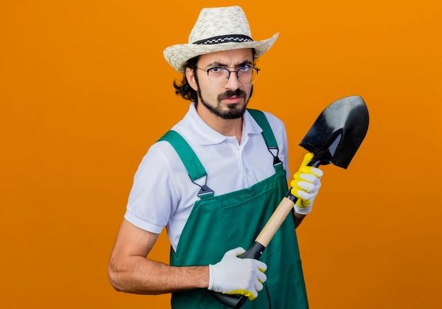 Jonge, gebaarde tuinmanmens die jumpsuit en de schop van de hoedholding draagt ?? die voorzijde met boos gezicht bekijkt dat zich over oranje muur bevindt Gratis Foto