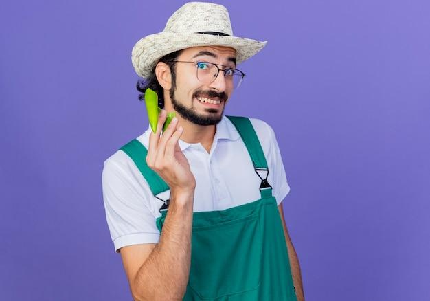 Jonge, gebaarde tuinmanmens die jumpsuit en hoed draagt die de helften van groene hete spaanse peperpeper toont die voorzijde glimlachend status over blauwe muur bekijkt