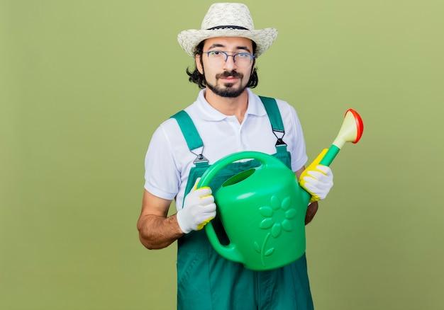 Jonge, gebaarde tuinmanmens die jumpsuit en hoed draagt die gieter houdt die voorzijde glimlachend zelfverzekerd over lichtgroene muur kijkt