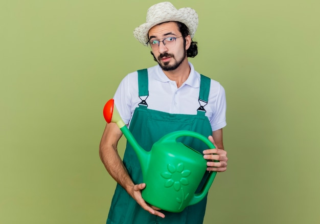 Jonge, gebaarde tuinmanmens die jumpsuit en hoed draagt die gieter houdt die voorzijde met droevige uitdrukking bekijkt die zich over lichtgroene muur bevindt