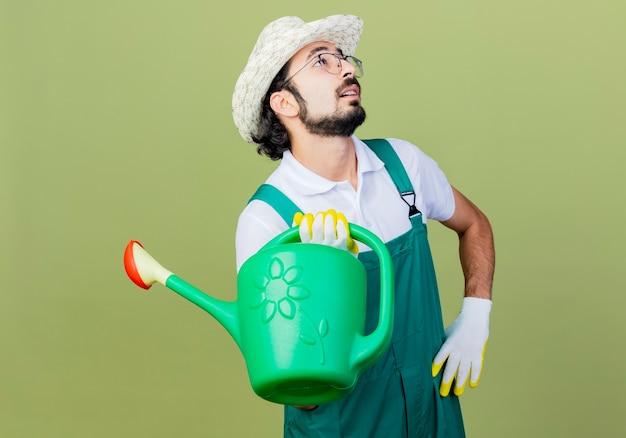 Jonge, gebaarde tuinmanmens die jumpsuit en hoed draagt die gieter houdt verbaasd omhoog kijkend status over lichtgroene muur