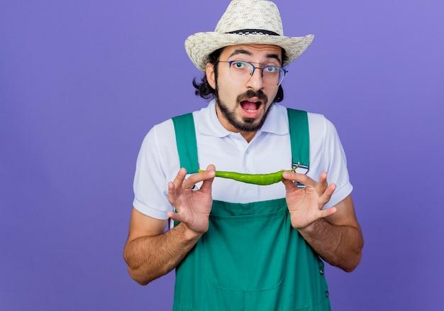 Jonge, gebaarde tuinmanmens die jumpsuit en hoed draagt die groene hete spaanse peperpeper toont die wordt verrast