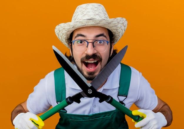 Jonge, gebaarde tuinmanmens die jumpsuit en hoed draagt die heggenschaar houdt die voorzijde glimlachend met gelukkig gezicht bekijkt dat zich over oranje muur bevindt