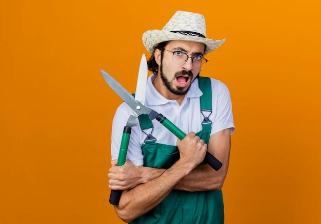 Jonge, gebaarde tuinmanmens die jumpsuit en hoed draagt die heggenschaar houdt die voorzijde met boos gezicht bekijkt dat zich over oranje muur bevindt