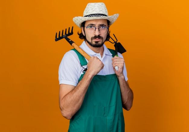 Jonge, gebaarde tuinmanmens die jumpsuit en hoed draagt die houweel en minihark houdt die voorzijde met ernstig gezicht bekijkt dat zich over oranje muur bevindt