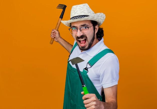 Jonge, gebaarde tuinmanmens die jumpsuit en hoed draagt die houweel en minihark houdt die voorzijde schreeuwt met boos gezicht dat zich over oranje muur bevindt