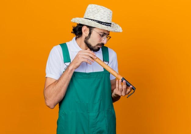 Jonge, gebaarde tuinmanmens die jumpsuit en hoed draagt die minihark houdt die ernaar kijkt geïntrigeerd staande over oranje muur