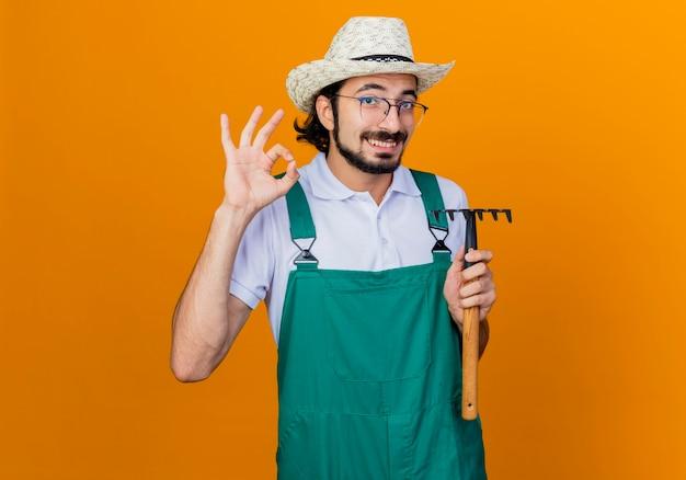 Jonge, gebaarde tuinmanmens die jumpsuit en hoed draagt die minihark houdt die voorzijde glimlachend toont die ok teken toont dat zich over oranje muur bevindt