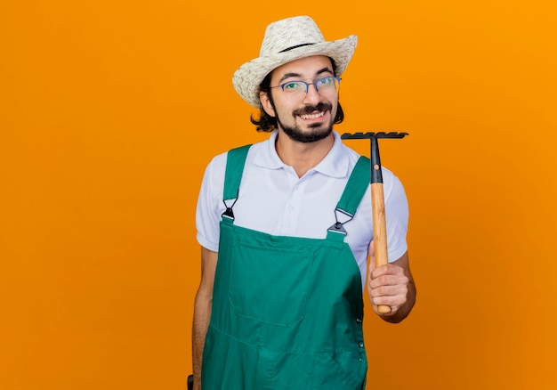 Jonge, gebaarde tuinmanmens die jumpsuit en hoed draagt die minihark houdt die voorzijde glimlachend vrolijk status over oranje muur bekijkt Gratis Foto