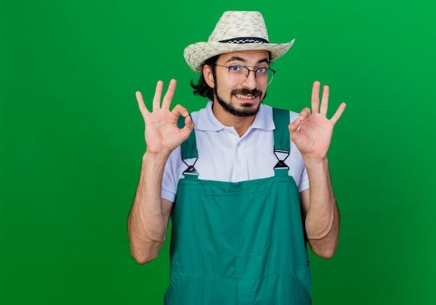 Jonge, gebaarde tuinmanmens die jumpsuit en hoed draagt die ok teken toont