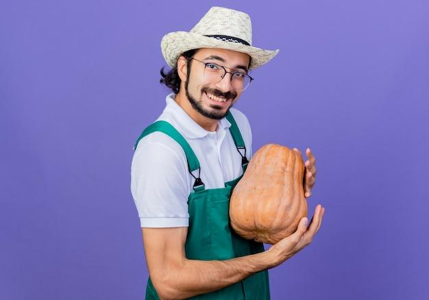 Jonge, gebaarde tuinmanmens die jumpsuit en hoed draagt die pompoen houdt die voorzijde glimlachend met gelukkig gezicht bekijkt dat zich over blauwe muur bevindt
