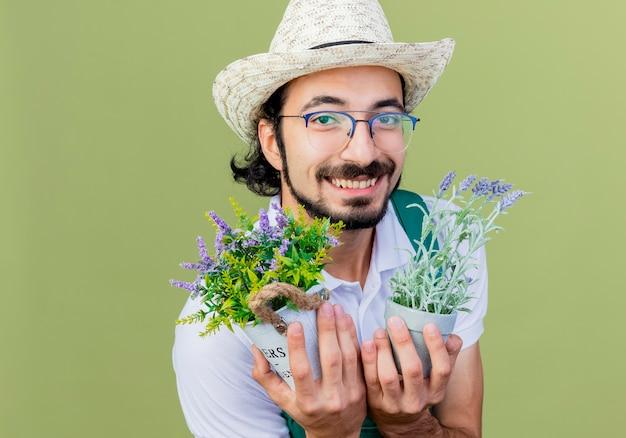 Jonge, gebaarde tuinmanmens die jumpsuit en hoed draagt die potplanten houdt die aan de voorkant glimlachen die vrolijk over de lichtgroene muur staat