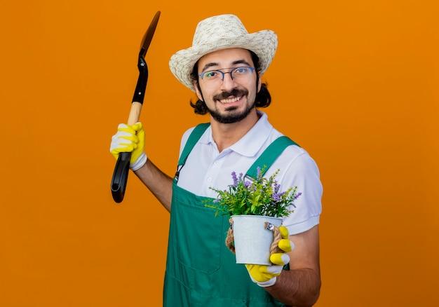 Jonge, gebaarde tuinmanmens die jumpsuit en hoed draagt die schop en potplant houdt die voorzijde glimlachend status over oranje muur bekijkt Gratis Foto
