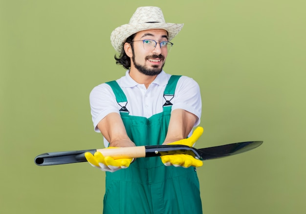 Jonge, gebaarde tuinmanmens die jumpsuit en hoed draagt die schop toont die voorzijde glimlachend status over lichtgroene muur bekijkt