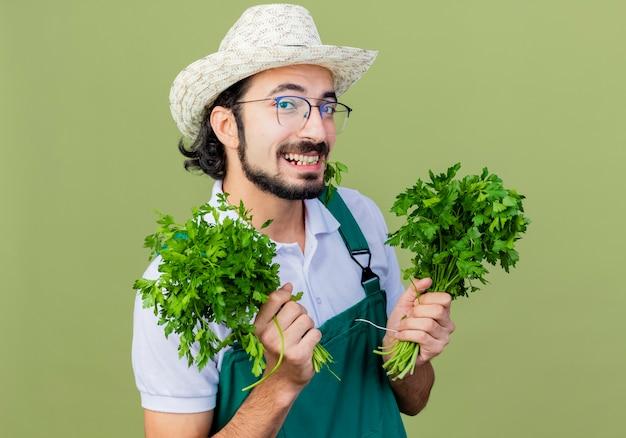 Jonge, gebaarde tuinmanmens die jumpsuit en hoed draagt die verse kruiden houdt die voorzijde glimlachend met gelukkig gezicht bekijkt dat zich over lichtgroene muur bevindt