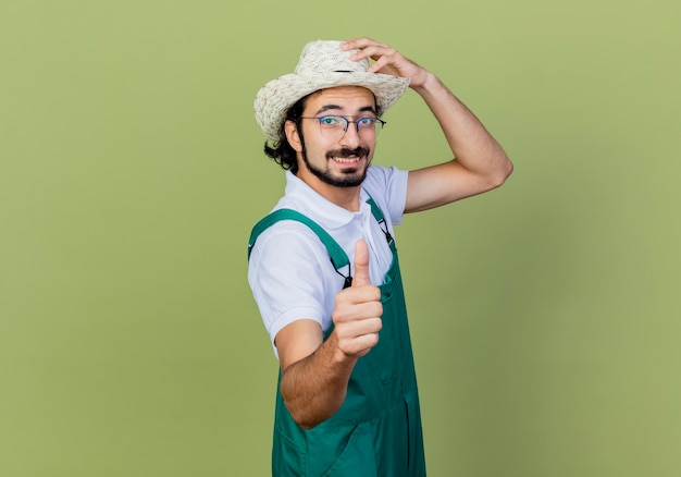 Jonge, gebaarde tuinmanmens die jumpsuit en hoed draagt die voorzijde glimlachen die duimen toont die zich over lichtgroene muur bevinden
