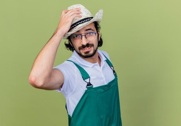 Jonge, gebaarde tuinmanmens die jumpsuit en hoed draagt die voorzijde glimlachend aanraken van zijn hoed die zich over lichtgroene muur bevindt