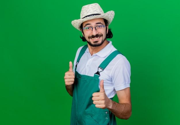 Jonge, gebaarde tuinmanmens die jumpsuit en hoed draagt die voorzijde glimlachend met gelukkig gezicht bekijkt dat duimen toont die zich over groene muur bevinden