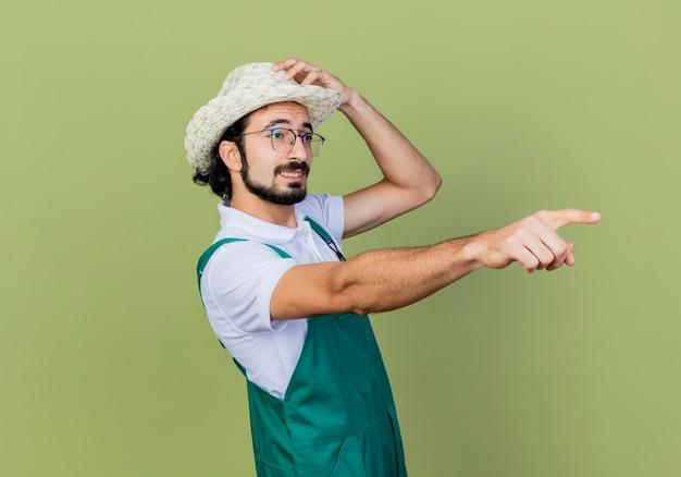 Jonge, gebaarde tuinmanmens die jumpsuit en hoed draagt wijst met wijsvinger naar iets dat zich over lichtgroene muur bevindt