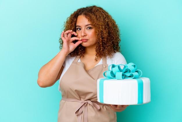 Jonge gebakje latijnse vrouw die een cake houdt die op blauwe achtergrond met vingers op lippen wordt geïsoleerd die een geheim houden.