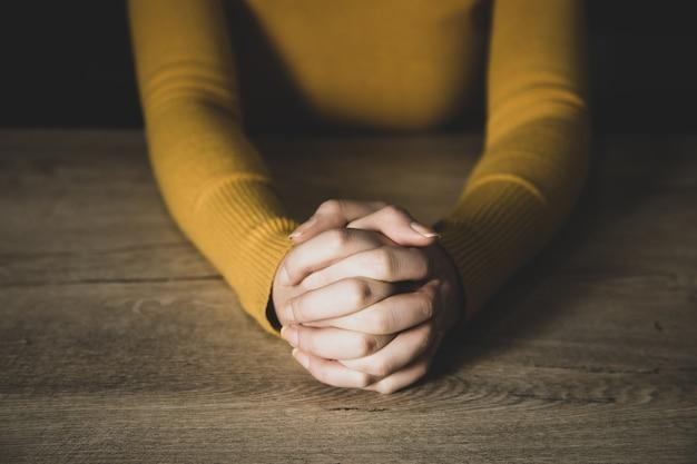 Jonge gebedsvrouw in donkere ruimte