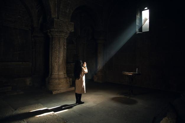 Jonge gebedsvrouw in kerk met licht
