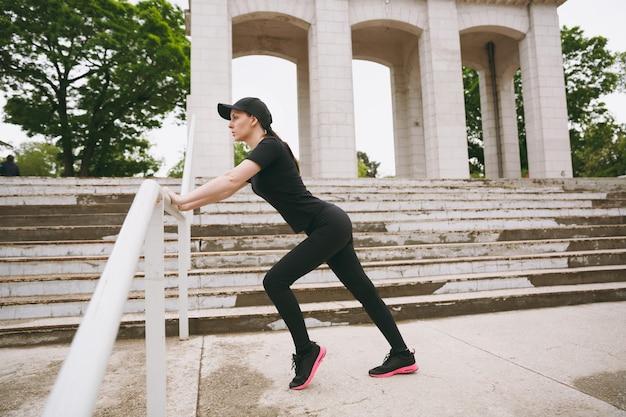 Jonge geconcentreerde atletische mooie brunette vrouw in zwart uniform en pet die sportrekoefeningen doet, opwarmen voordat ze in het stadspark buiten rennen running