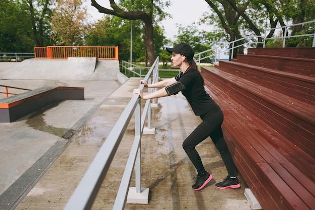 Jonge geconcentreerde atletische mooie brunette vrouw in zwart uniform, pet met koptelefoon luisteren naar muziek sport stretchoefeningen opwarmen in stadspark buitenshuis