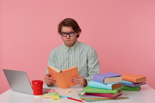 Jonge geconcentreerde man in bril draagt in shirt, zit bij de tafel en werkt met laptop, voorbereid voor examen, boek leest, ziet er serieus uit, geïsoleerd op roze achtergrond.