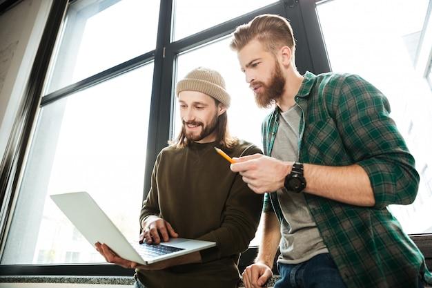 Jonge geconcentreerde mannen collega's in kantoor met behulp van laptop