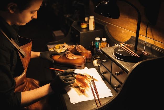 Jonge geconcentreerde mensenschoenmaker op schoeiselworkshop.