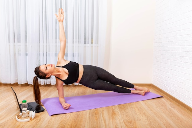 Jonge geconcentreerde vrouw die yogaoefeningen doet die laptop met behulp van