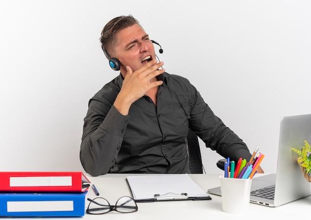 Jonge geërgerd blonde kantoormedewerker man op koptelefoon zit aan bureau met office-hulpprogramma's met behulp van laptop schreeuwt naar iemand kijken kant geïsoleerd op een witte achtergrond met kopie ruimte