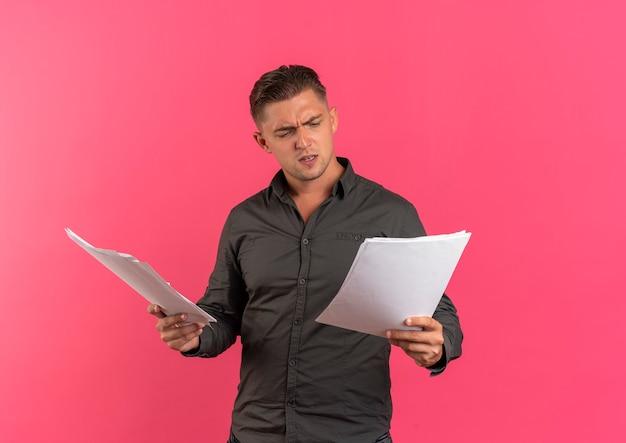 Jonge geërgerd blonde knappe man houdt en kijkt naar vellen papier geïsoleerd op roze achtergrond met kopie ruimte