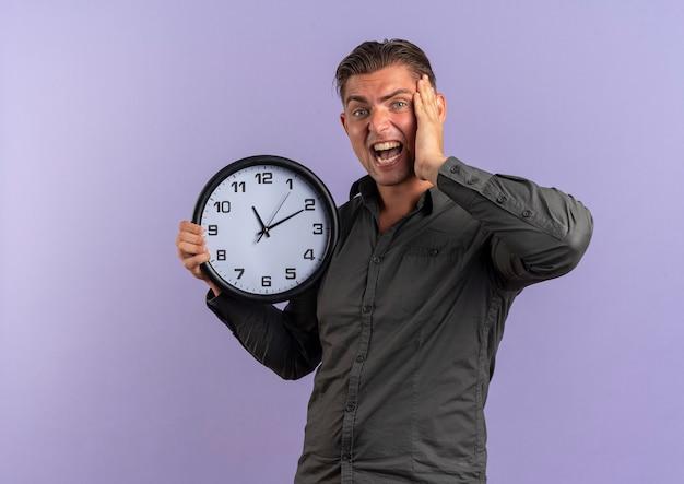 Jonge geërgerd blonde knappe man houdt klok en legt hand op gezicht geïsoleerd op violette achtergrond met kopie ruimte