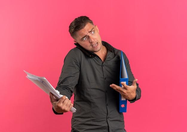 Jonge geërgerd blonde knappe man houdt vellen papier en map praten over telefoon geïsoleerd op roze ruimte met kopie ruimte