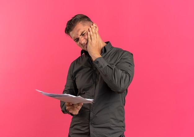 Jonge geërgerd blonde knappe man legt hand op gezicht en kijkt naar vel papier geïsoleerd op roze achtergrond met kopie ruimte
