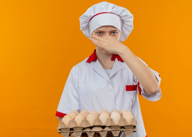 Jonge geërgerd blonde vrouwelijke chef-kok in uniform chef houdt partij eieren en sluit neus met hand geïsoleerd op oranje muur
