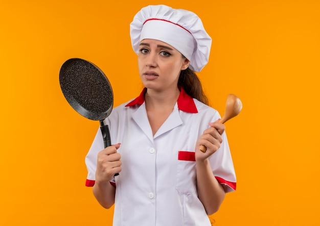 Jonge geërgerde blanke kok meisje in uniform chef houdt koekenpan en houten lepel geïsoleerd op een oranje achtergrond met kopie ruimte