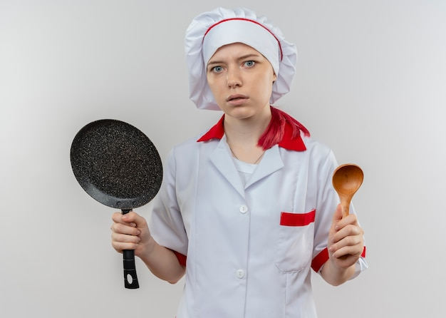 Jonge geërgerde blonde vrouwelijke chef-kok in uniform chef houdt koekenpan en lepel geïsoleerd op een witte muur