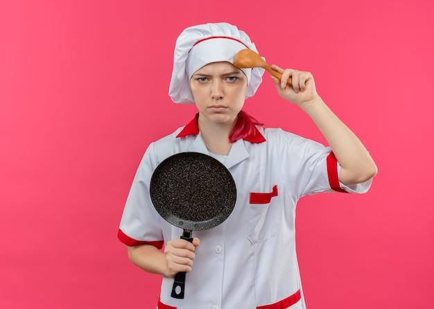 Jonge geërgerde blonde vrouwelijke chef-kok in uniform chef houdt koekenpan en zet lepel op hoofd geïsoleerd op roze muur