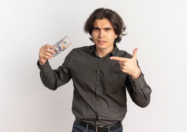 Jonge geërgerde knappe blanke man houdt en wijst op geld geïsoleerd op een witte achtergrond met kopie ruimte