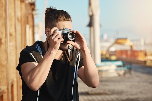 Jonge gefocuste europese kerel die zich in haven bevindt die door camera kijkt terwijl het nemen van beelden van zee of jachten, lopend langs stad om koele foto's voor tijdschrift te verzamelen. getalenteerde cameraman zoekhoek