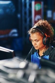 Jonge gefocuste gemengd ras meisje vrouwelijke cybersport gamer die een koptelefoon draagt die deelneemt aan esport