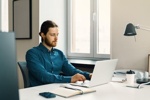 Jonge gefocuste man freelancer die op afstand op laptopcomputer werkt