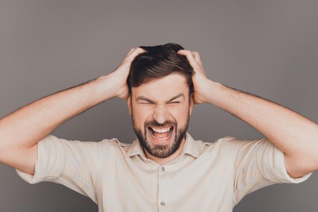 Jonge gefrustreerde boze zakenman met grote problemen schreeuwen