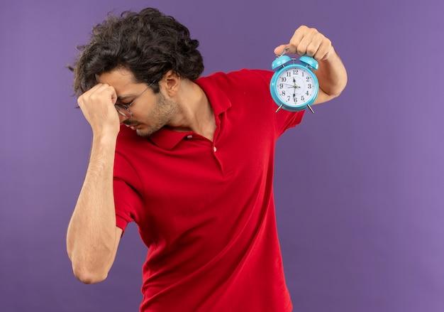Jonge gefrustreerde man in rood shirt met optische bril houdt klok vast en legt hand op gezicht geïsoleerd op violette muur