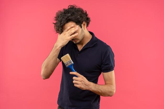 Jonge gefrustreerde man in zwart shirt met optische bril legt hand op gezicht en houdt penseel geïsoleerd op roze muur