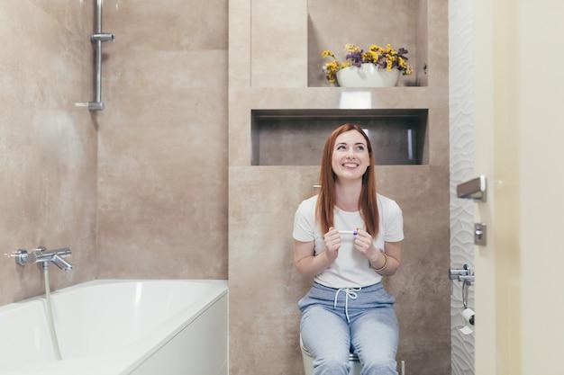Jonge gefrustreerde vrouw die naar een snelle positieve of negatieve zwangerschapstest kijkt